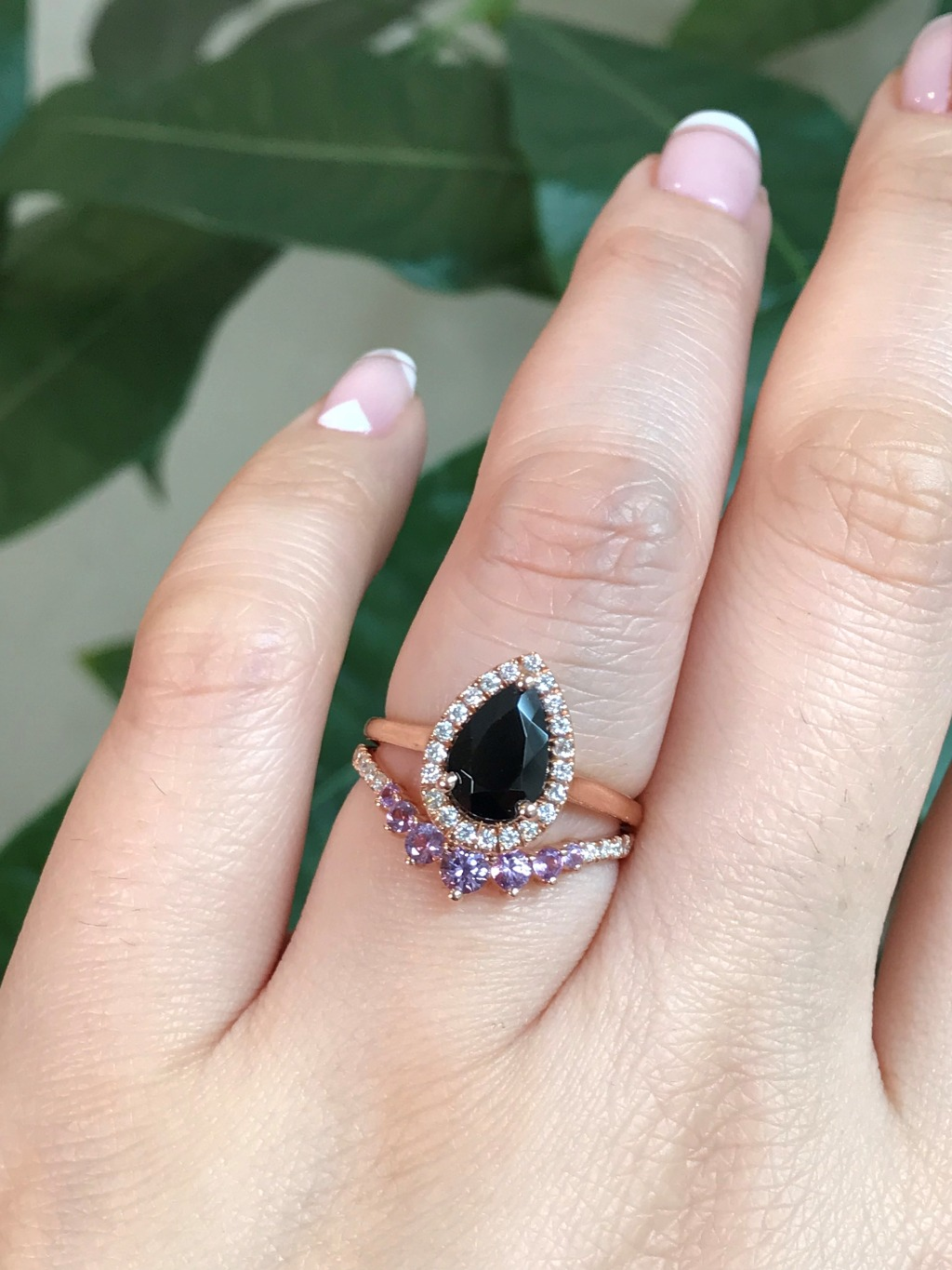 This halo diamond ring bridal set showcases a pear cut black spinel diamond engagement ring in 14k rose gold halo diamond ring setting