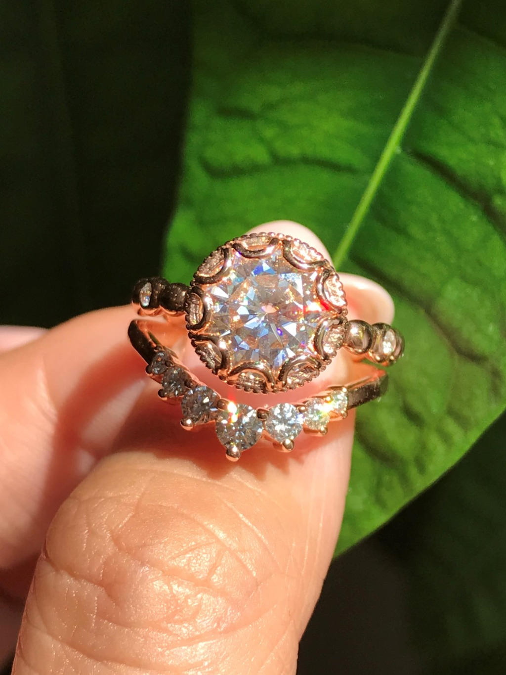 Elegant bridal set of a round cut moissanite engagement ring in 14k rose gold floral ring setting pairs gorgeously with a curved 7