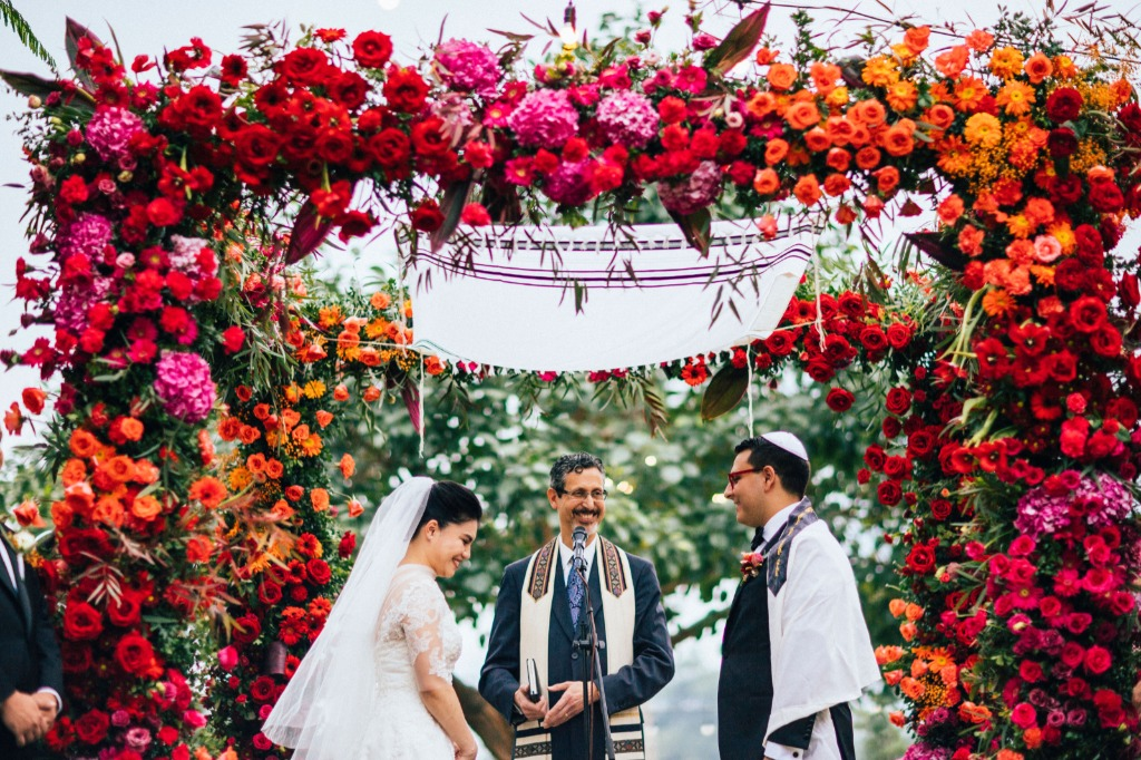 A vivid, blooming flower chuppah in a Jewish wedding ceremony that instantly grabs your attention. No need to pull it back, The bride