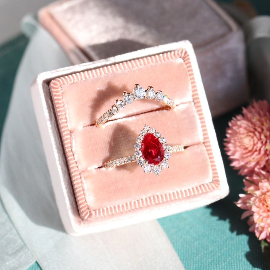 Breathtakingly gorgeous Tiara Halo Ruby bridal set showcases a 8x5mm pear cut ruby set in our Tiara Halo Diamond ring setting with