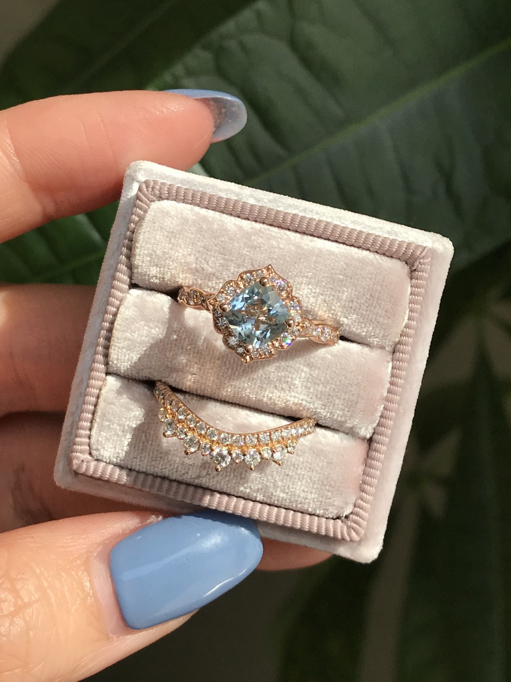 This bridal set showcases a mini vintage floral engagement ring with a 6x6mm cushion cut aquamarine set in 14k Rose Gold. To complete