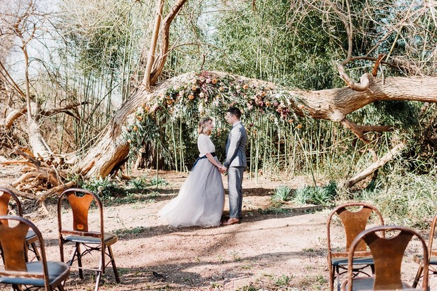 outdoor wedding ceremony with floral backdrop
