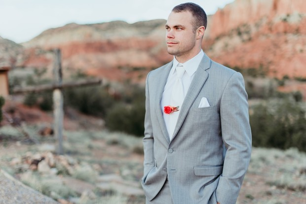 groom style with floral tie clip