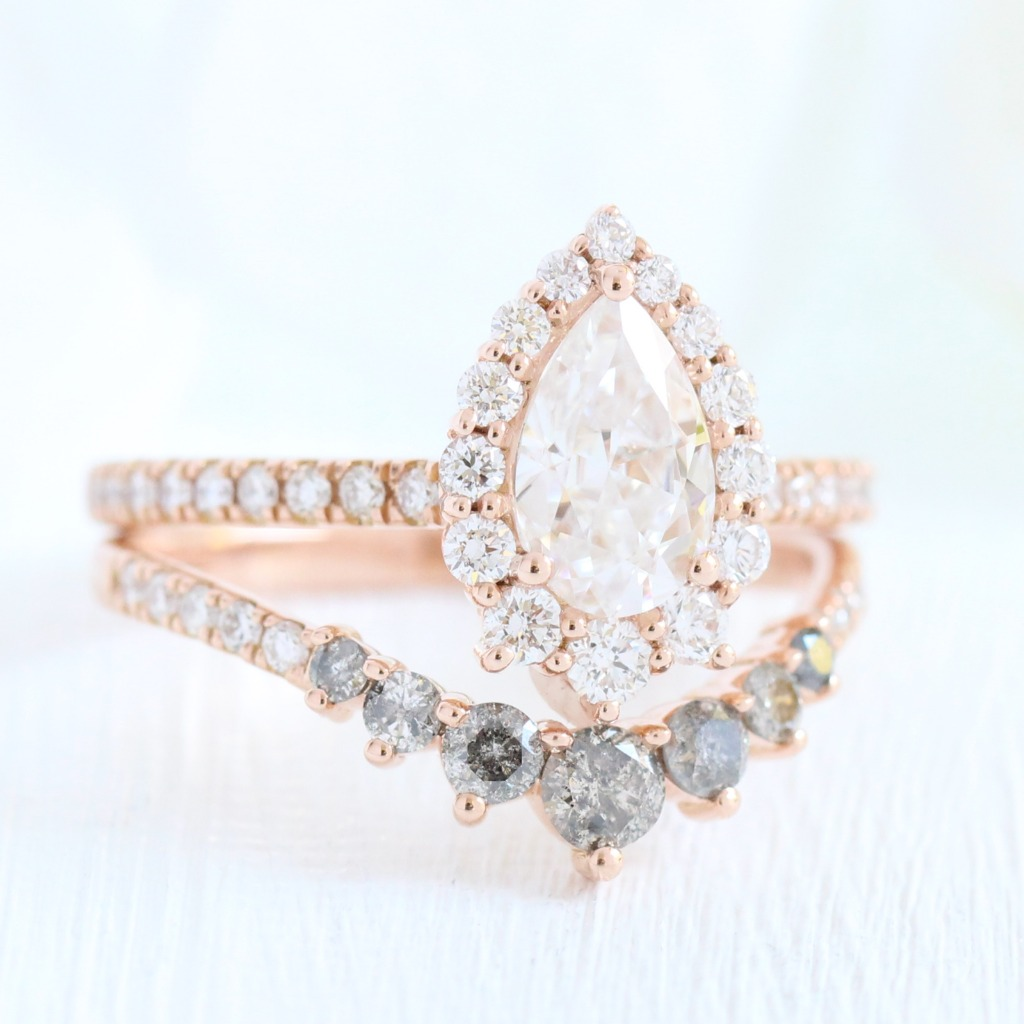 Gorgeous bridal ring set of a pear cut forever one moissanite engagement ring in 14k rose gold halo diamond ring setting pairs gorgeously