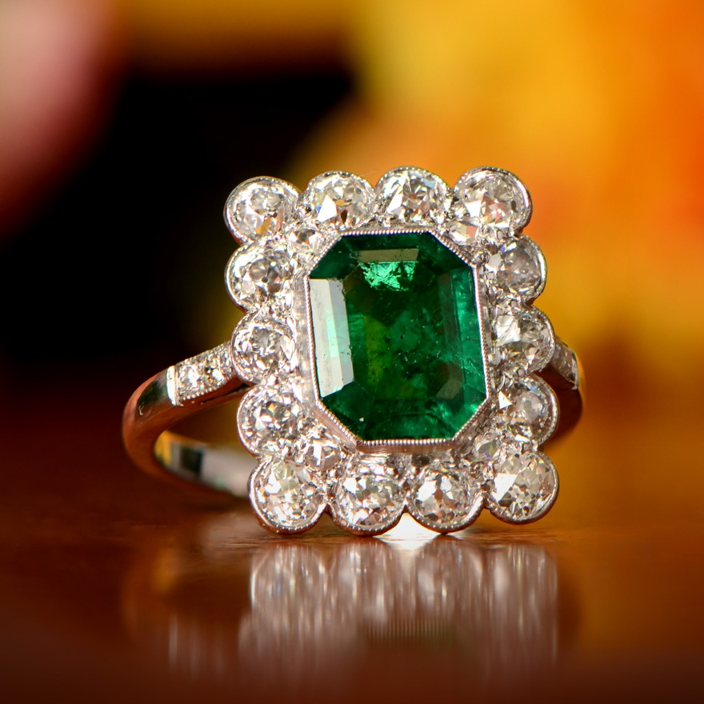An impressive Art Deco Era ring centering a 1.70-carats Colombian emerald and surrounded by 1.00 carats of diamonds. Circa 1920.