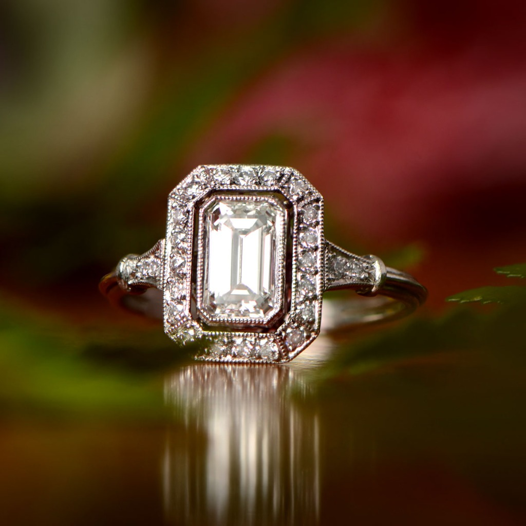 A beautiful and bold diamond engagement ring, featuring a stunning emerald-cut diamond and surrounded by a halo of diamonds. Curated