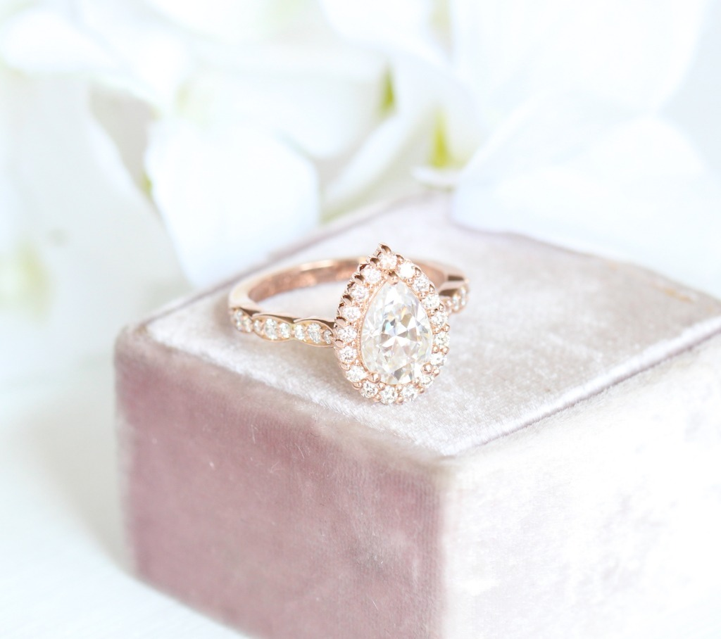 Timelessly elegant moissanite engagement ring features a 9x6mm pear cut Forever One Moissanite set in 14k rose gold halo diamond ring