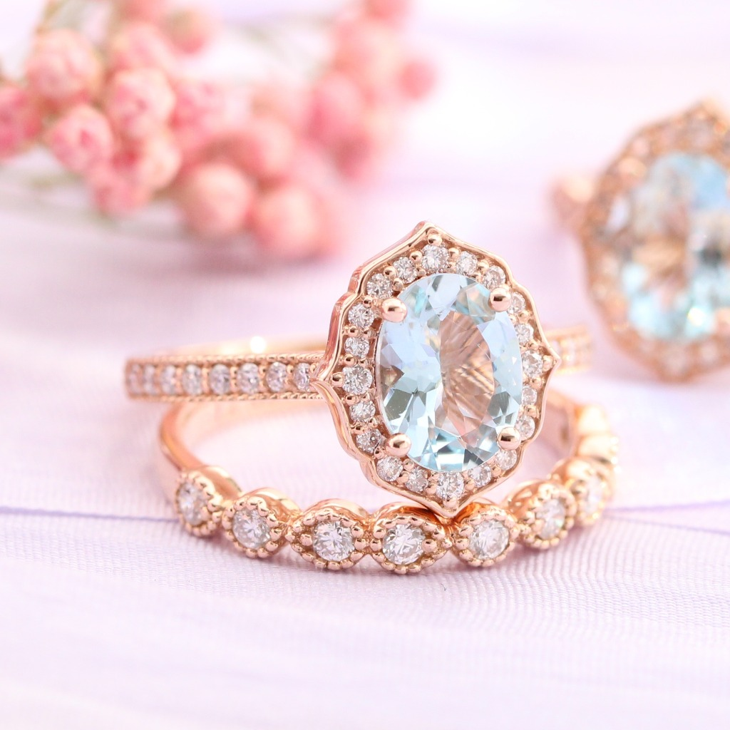 Artfully sculpted bridal ring set of an oval cut aquamarine engagement ring in 14k rose gold vintage floral ring setting pairs gorgeously