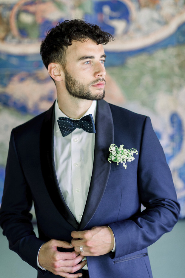 groom in navy suite and polka dot bow tie