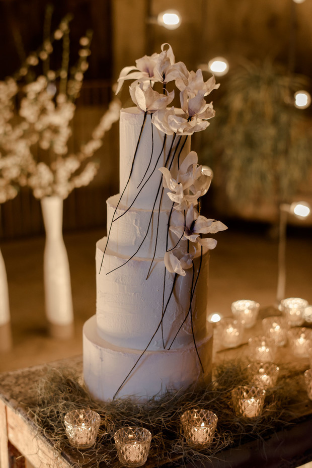 dramatic wedding cake with floral decor and candle light