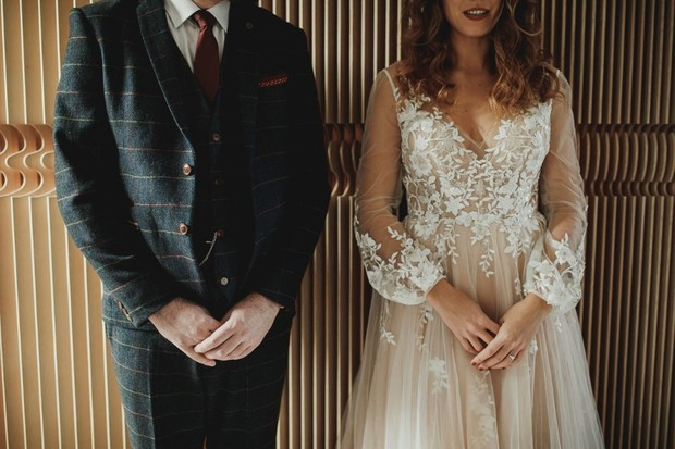 groom in gold print suit and bride in romantic dress