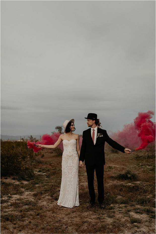 hipster couple in the desert with red smoke bombs