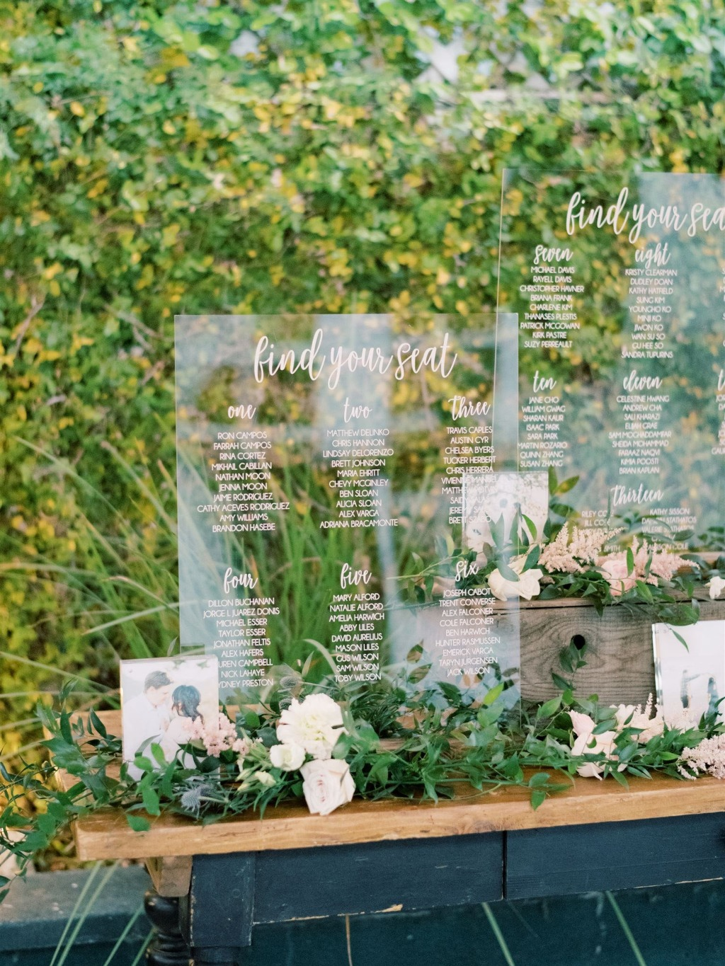 This seating chart set up is gorgeous! Love the clear acrylic against the greenery backdrop.