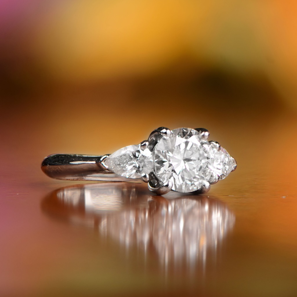 A beautiful Tiffany & Co. diamond engagement ring, featuring a round diamond in the center which is flanked by pear-cut diamonds