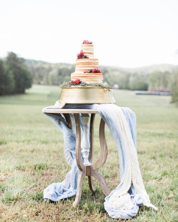 naked wedding cake topped with berries