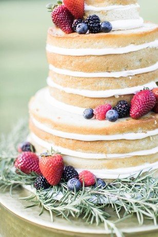 naked wedding cake topped with fresh berries