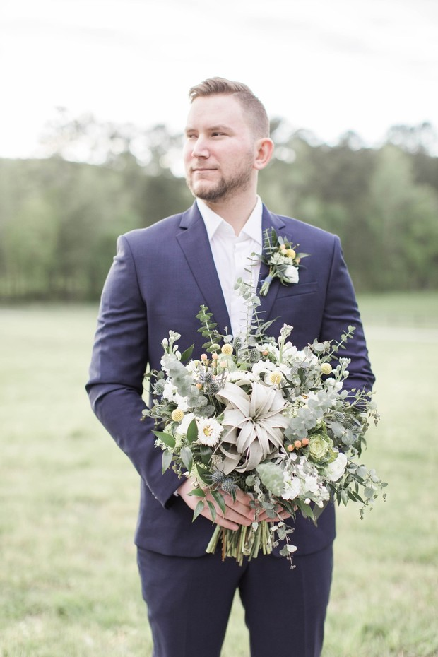 groom in suit and no tie with bridal bouquet