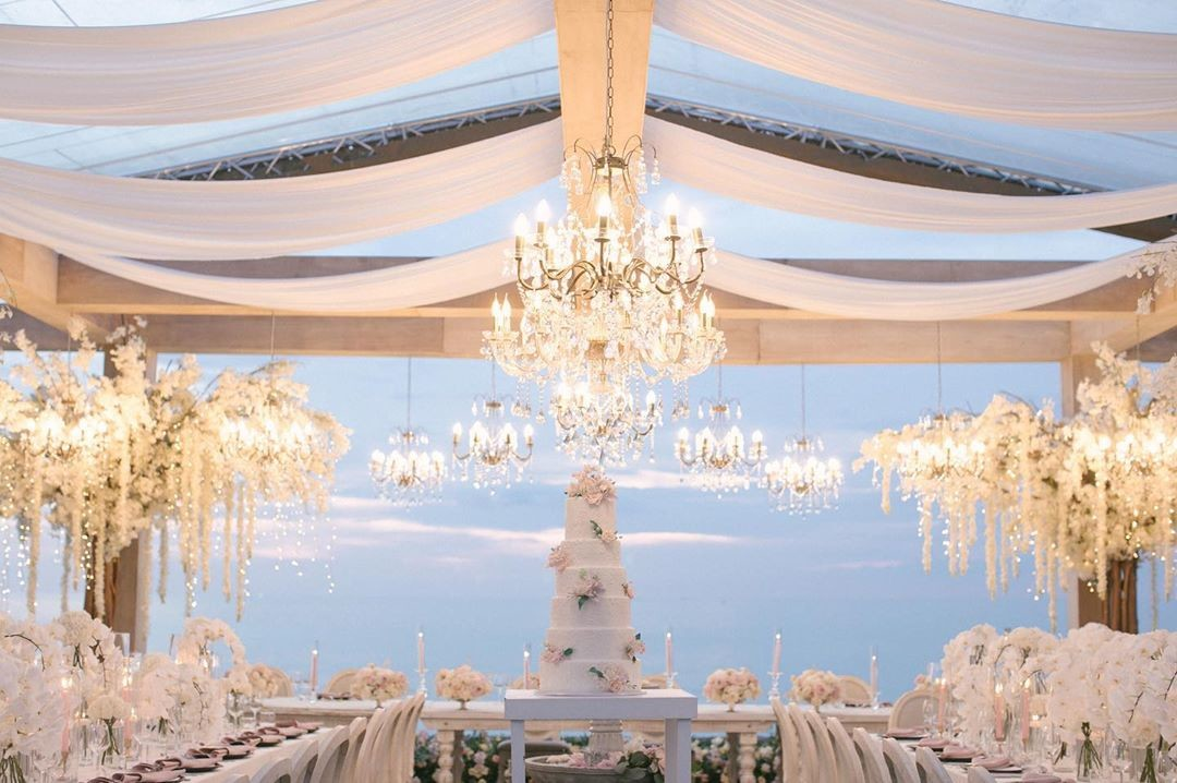 Our all-white reception with chandelier lights and cascading orchid branches — Modern setting with classical references. Macy &