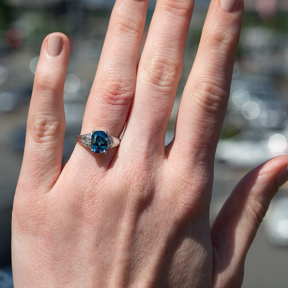 This lovely engagement ring features a bi-color no heat 2.6ct sapphire in a platinum engraved setting with square French cut side diamonds