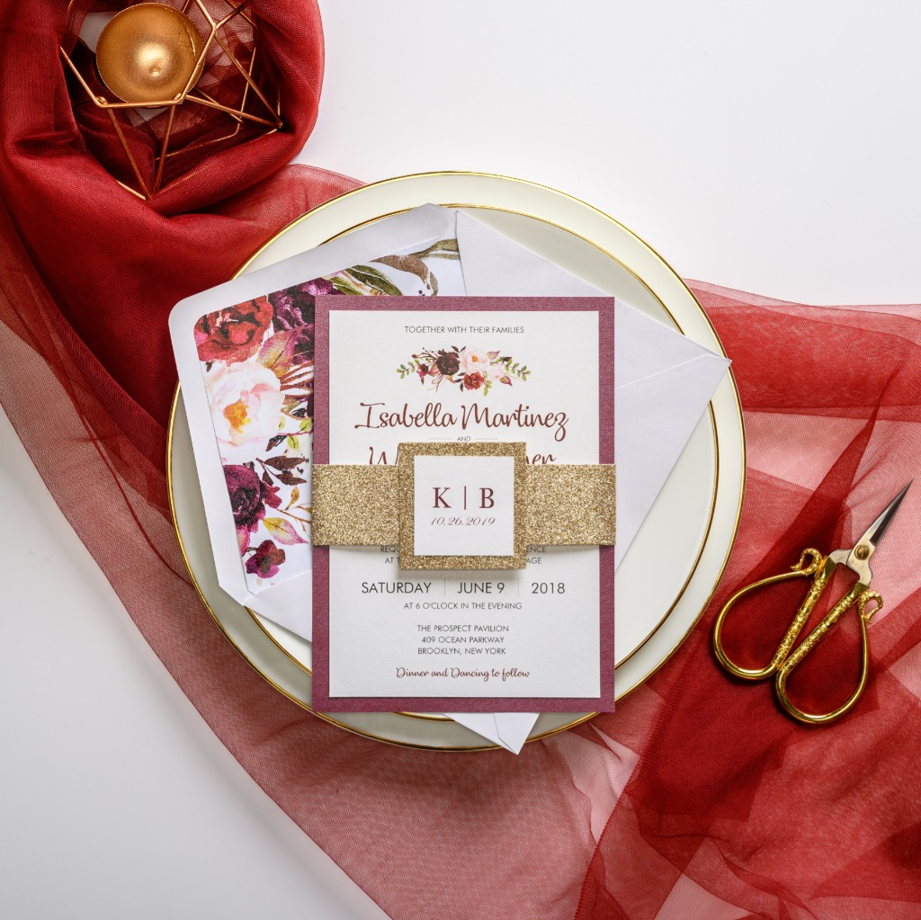 Gold shimmer belly band, burgundy edge, watercolor floral pattern together make up this elegant wedding invitation. Perfect for any