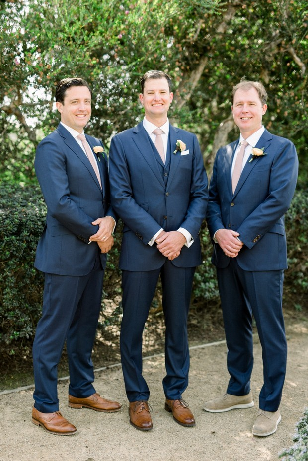 groom and his men in navy blue suits and blush ties