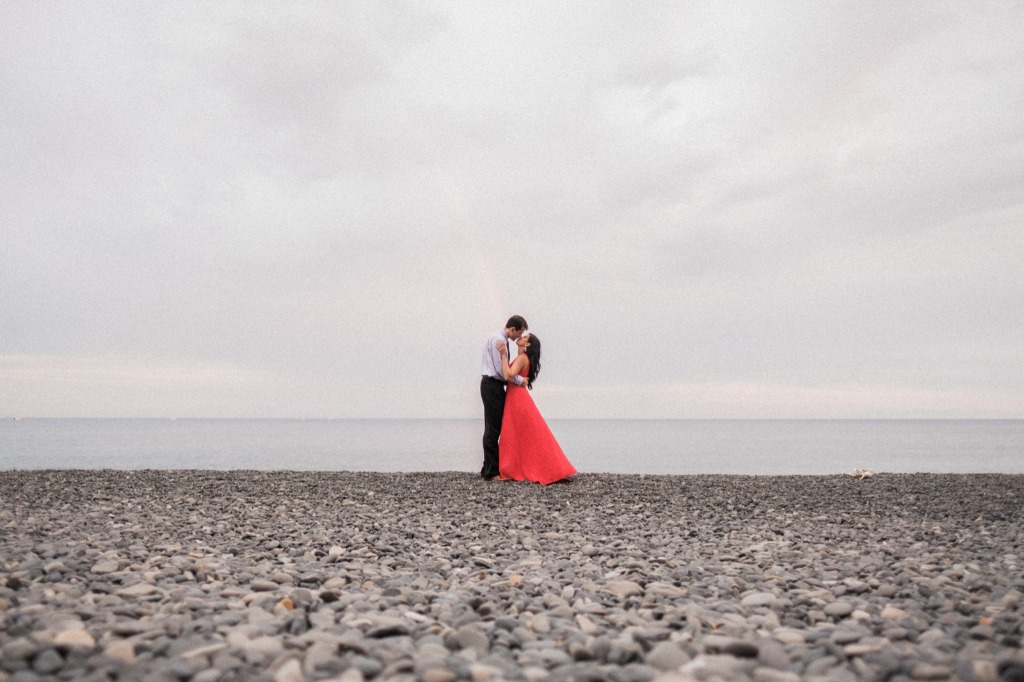 The pebbles are black, the dress is red, their love is unique under the rainbow's arch of colours. The most romantic moment one day