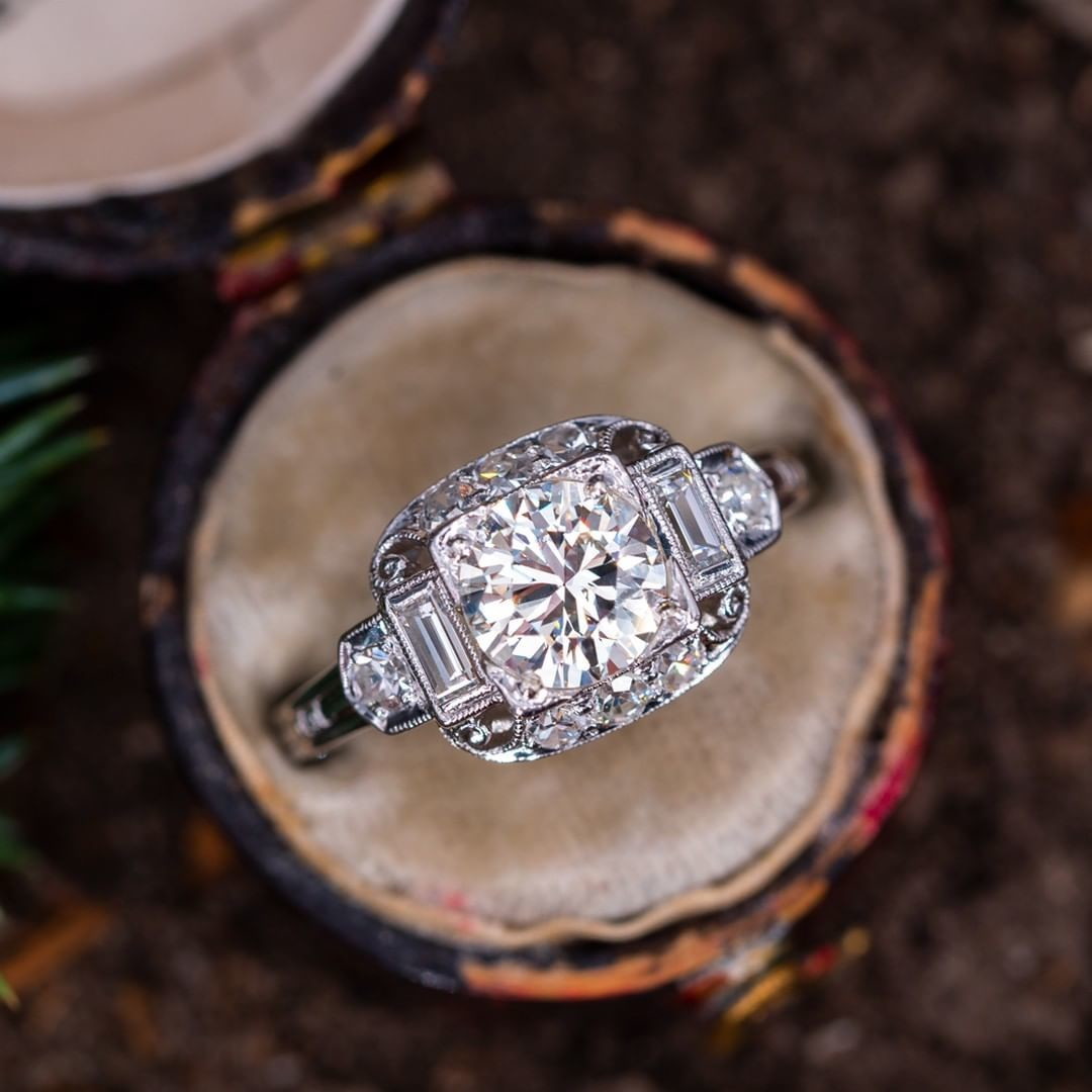 Vintage Engagement Ring w/ Intricate Detailing. The center diamond grades K in color and VVS2 in clarity. There are two baguette side