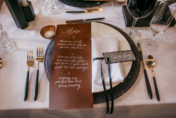 leather menu and black and white place setting