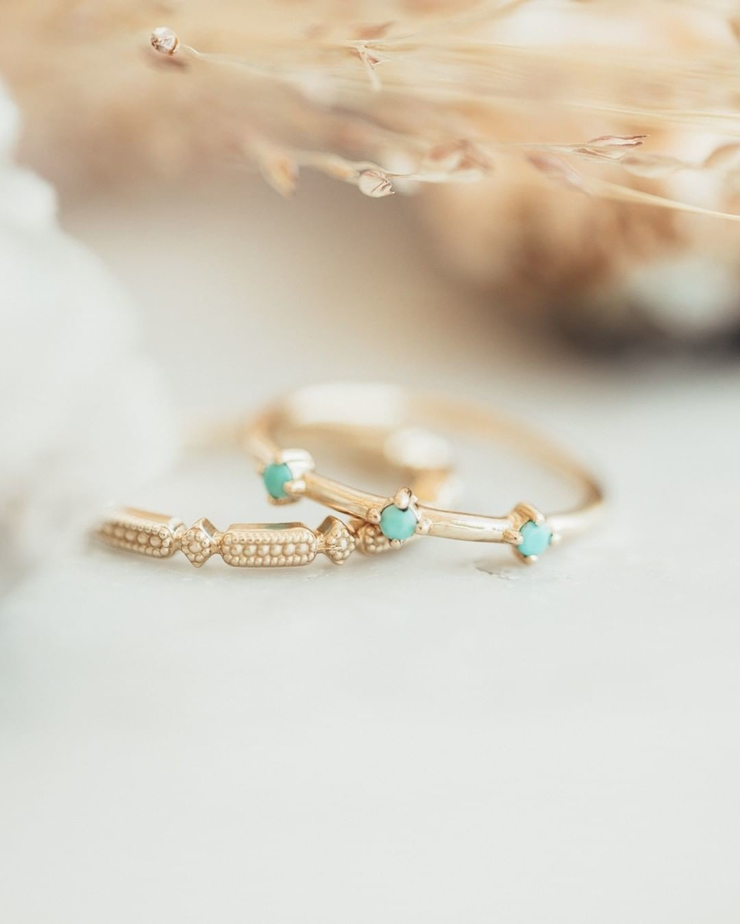 Swooning over this stack! Our turquoise three stone ring in yellow gold pairs perfectly with this vintage inspired milgrain band. Come