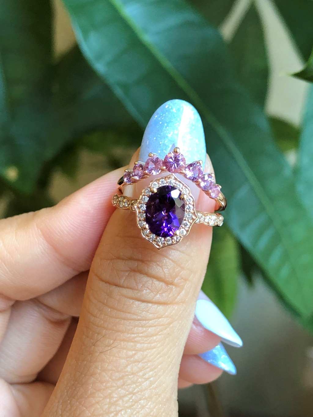 Unique yet elegant purple amethyst bridal set showcases a oval cut amethyst engagement ring in 14k rose gold floral ring setting and