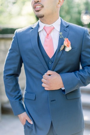 groom in blue suit and coral tie