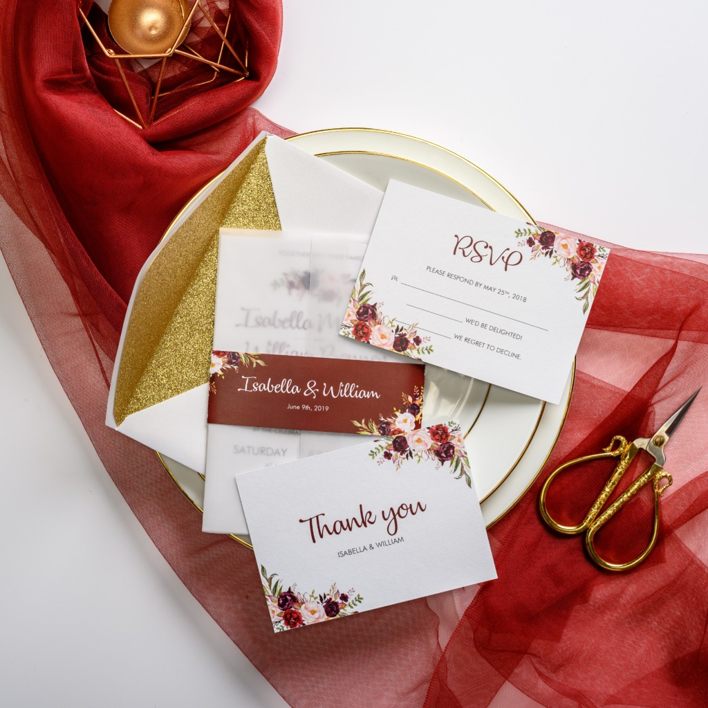 This elegant wedding invitation features white vellum wrap accented with burgundy belly band and floral pattern scattered around the