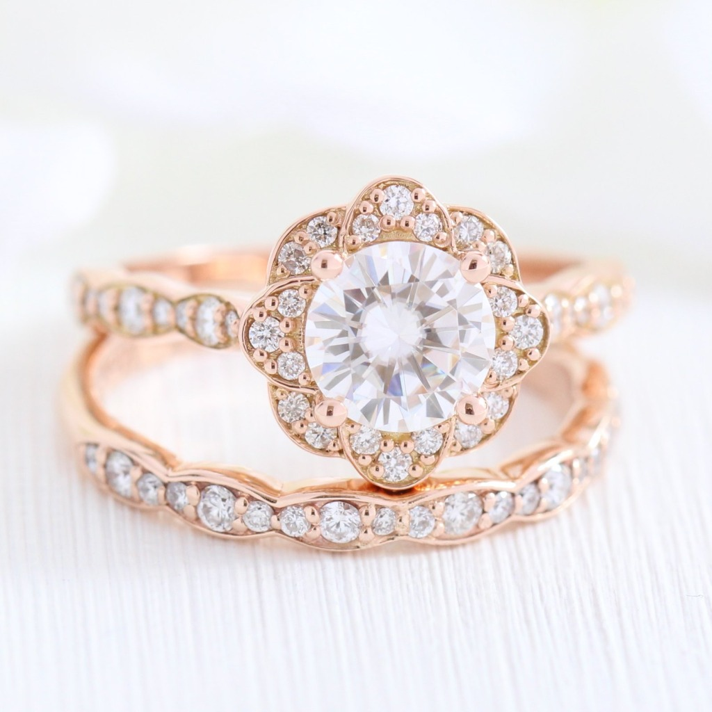 Elegant and classic moissanite bridal ring set showcases a vintage floral moissanite engagement ring with a one carat round cut Forever