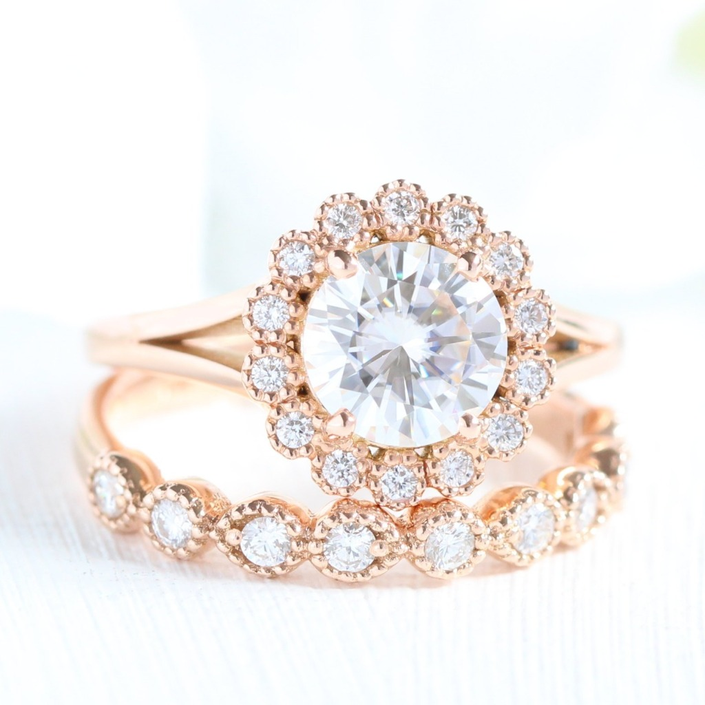 Breathtaking bridal ring set of a Vintage Inspired Engagement Ring showcases a Round Cut Moissanite in 14k rose gold Halo Diamond Ring