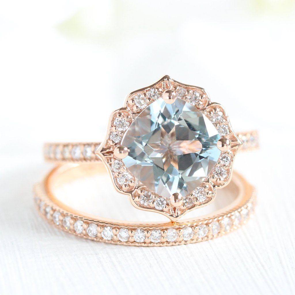 This vintage style bridal set showcases a 8x8mm cushion cut aquamarine engagement ring in 14k rose gold vintage floral ring setting