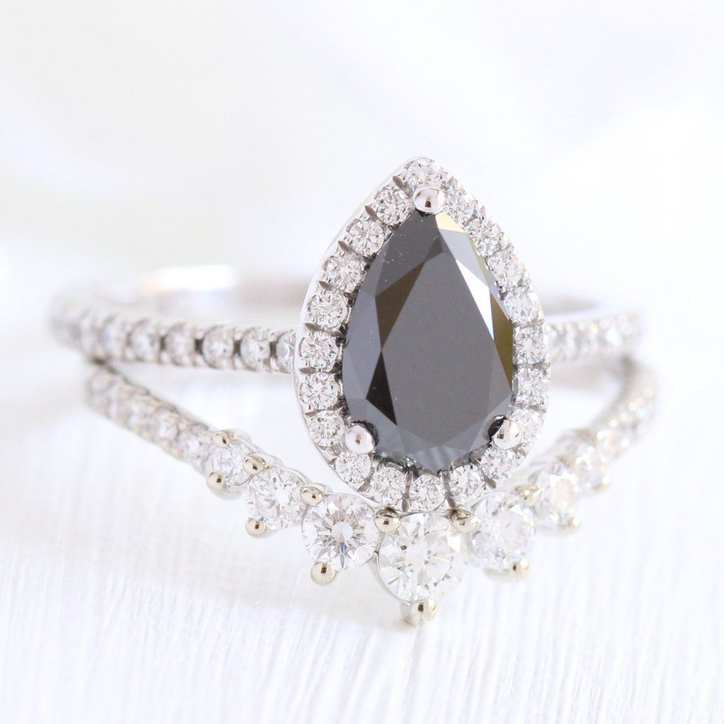 Artfully crafted black diamond bridal set features a pear black diamond engagement ring in 14k white gold luna halo diamond ring setting
