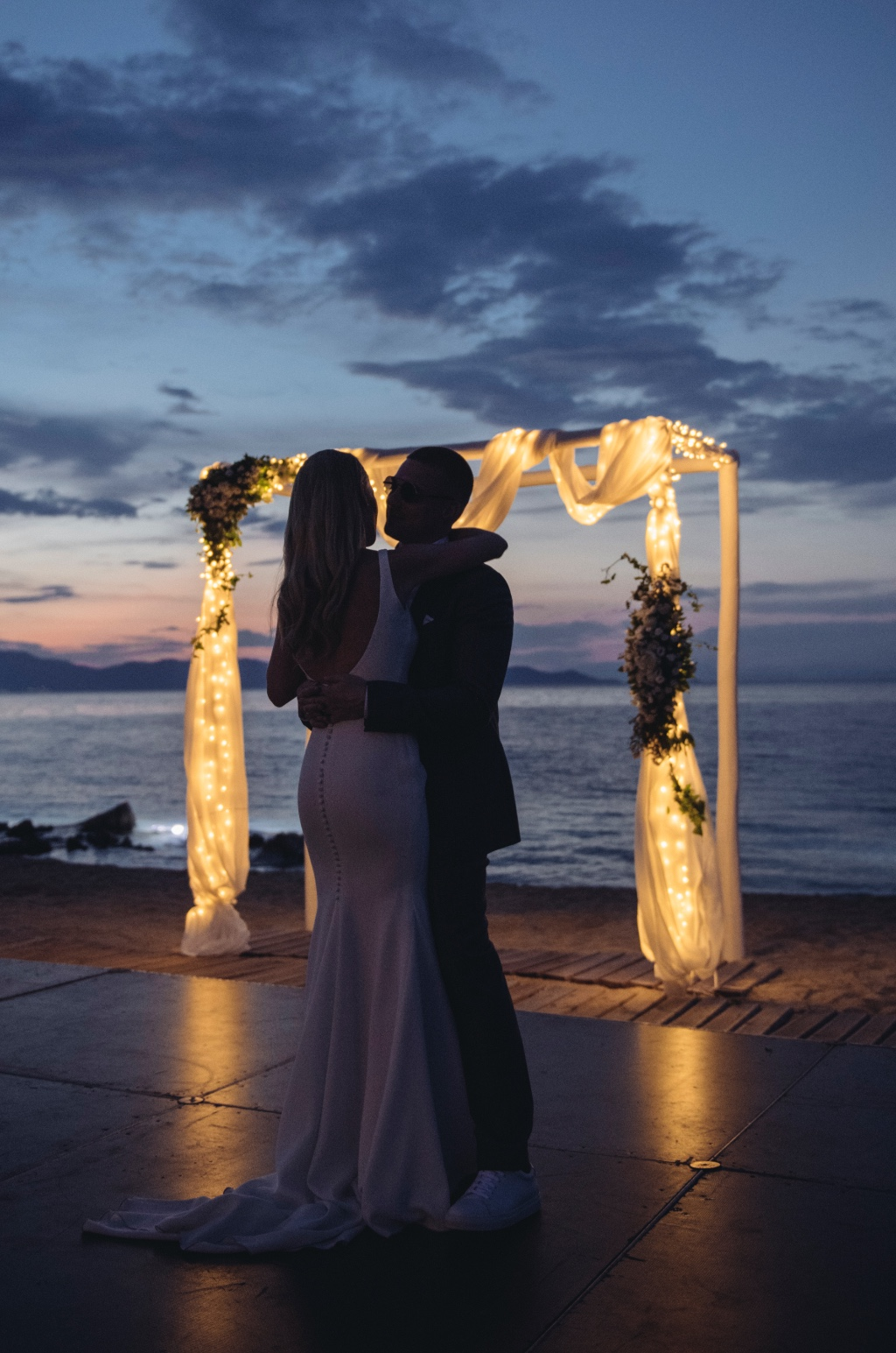 string lights on wedding floral arch on the beach at Avaton Luxury Villas Resort- Relais & Chateaux