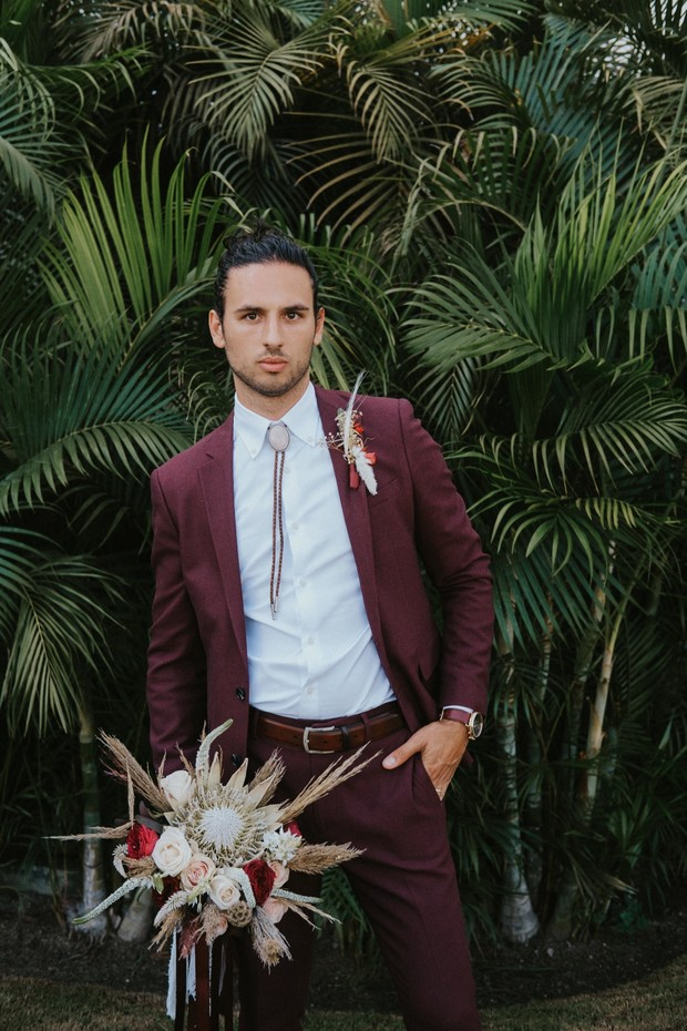 groom in burgundy suit