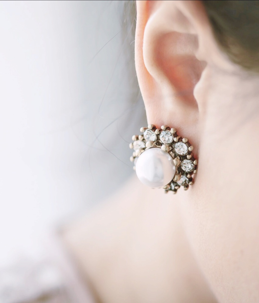 The Evelyn Pearl Stud Earrings feature a large pearl surrounded by sparkling crystals. These vintage style pearl stud wedding earrings