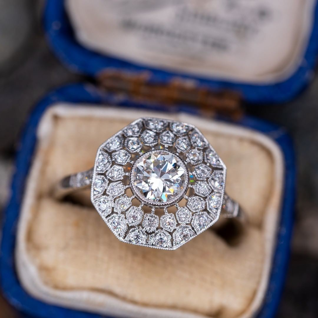 This lovely handmade ring features a transitional cut center diamond and beautiful openwork and milgrain detailing.
