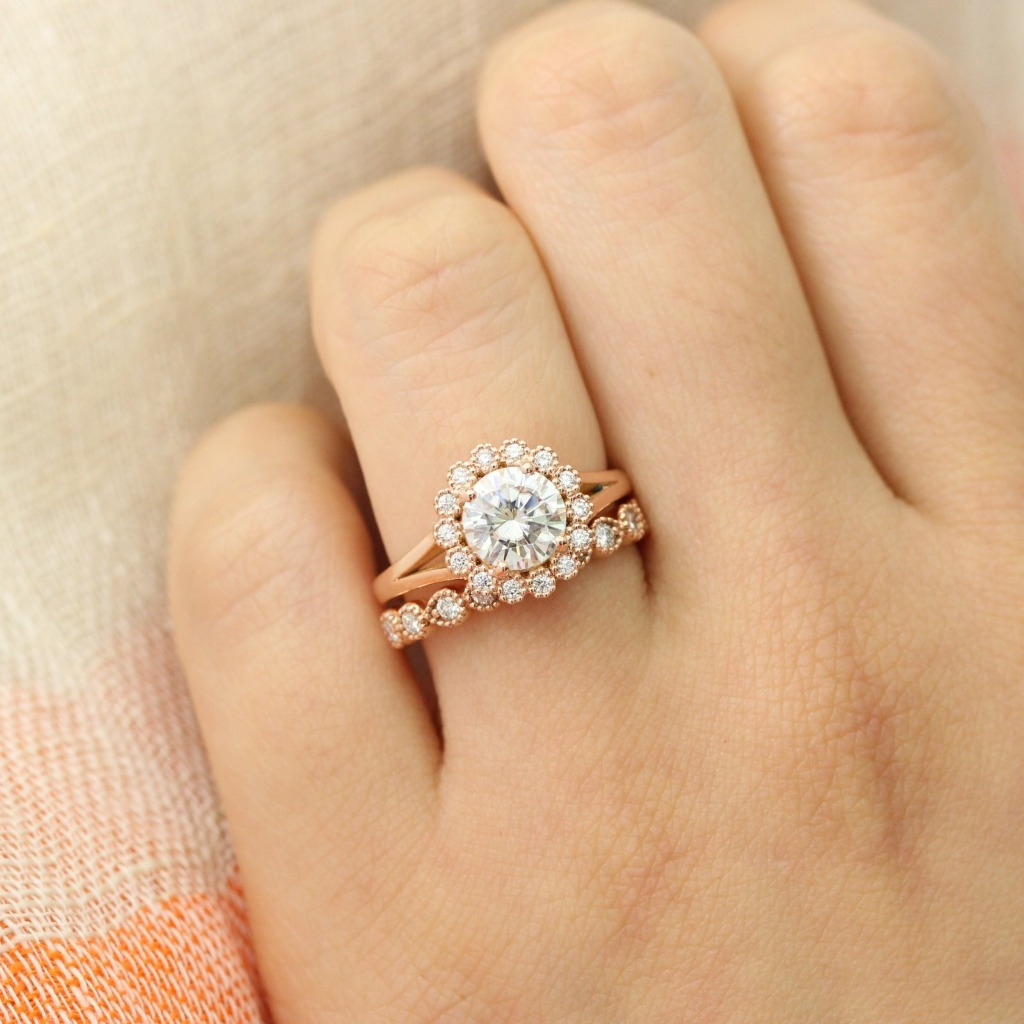 Vintage inspired bridal ring set of a round cut moissanite engagement ring in 14k rose gold halo diamond ring setting and completed