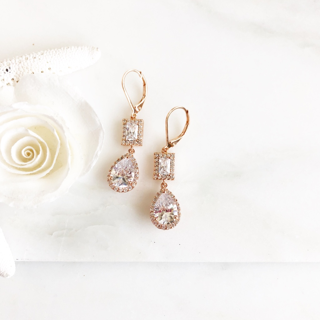 The stones are glass and cublic zirconia set in rose gold plated brass. The earrings hang about 1.35 long.