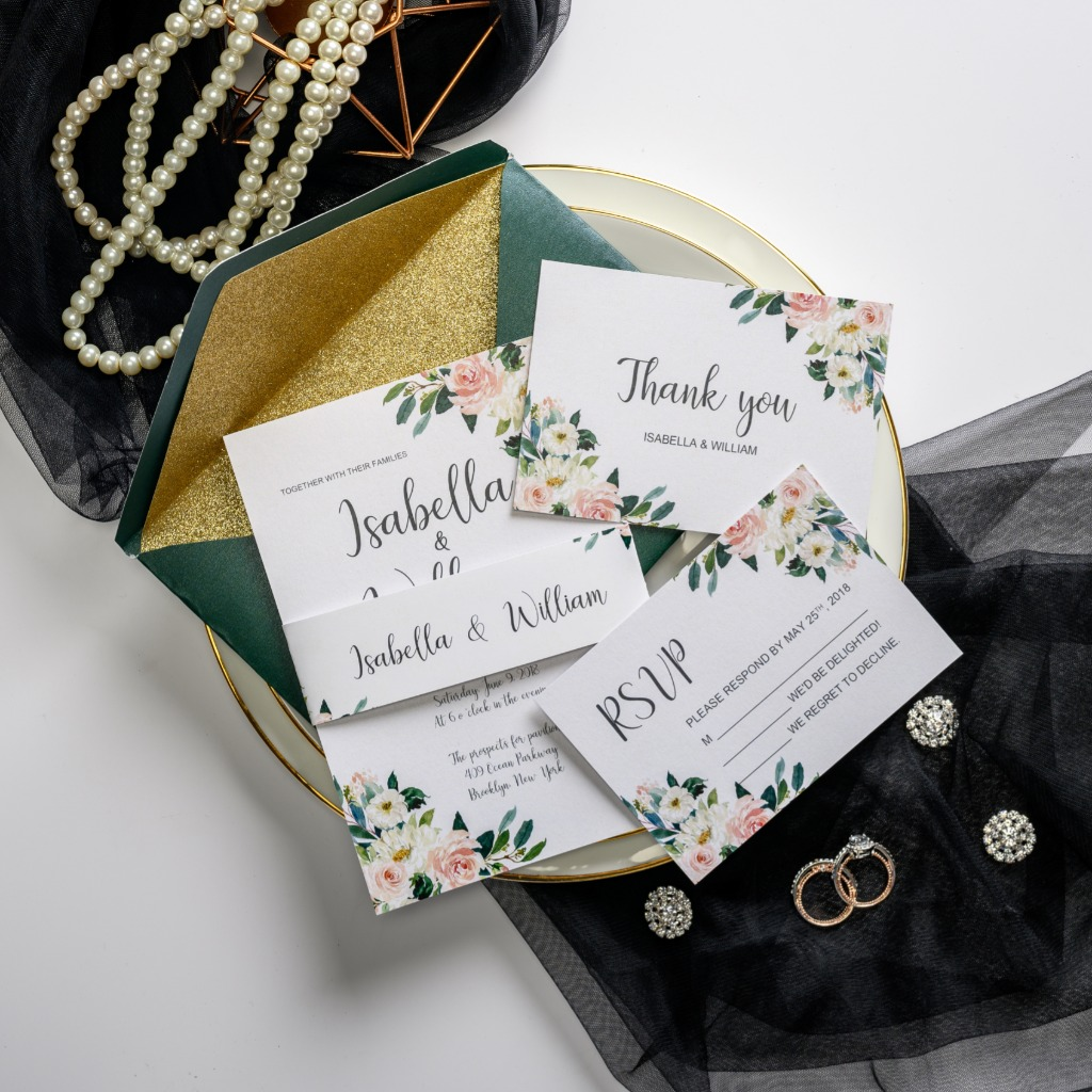 White wedding invitation features gorgeous painted florals and chic belly band. Soft pink watercolor florals and lovely greenery make
