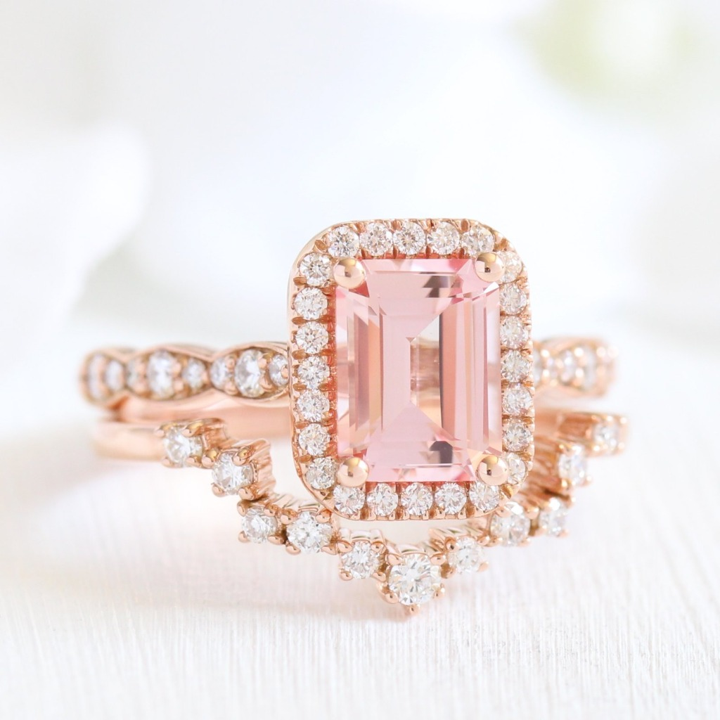 Gracefully handcrafted peach sapphire ring bridal set features a 8x6mm emerald cut conflict free cultured champagne peach sapphire