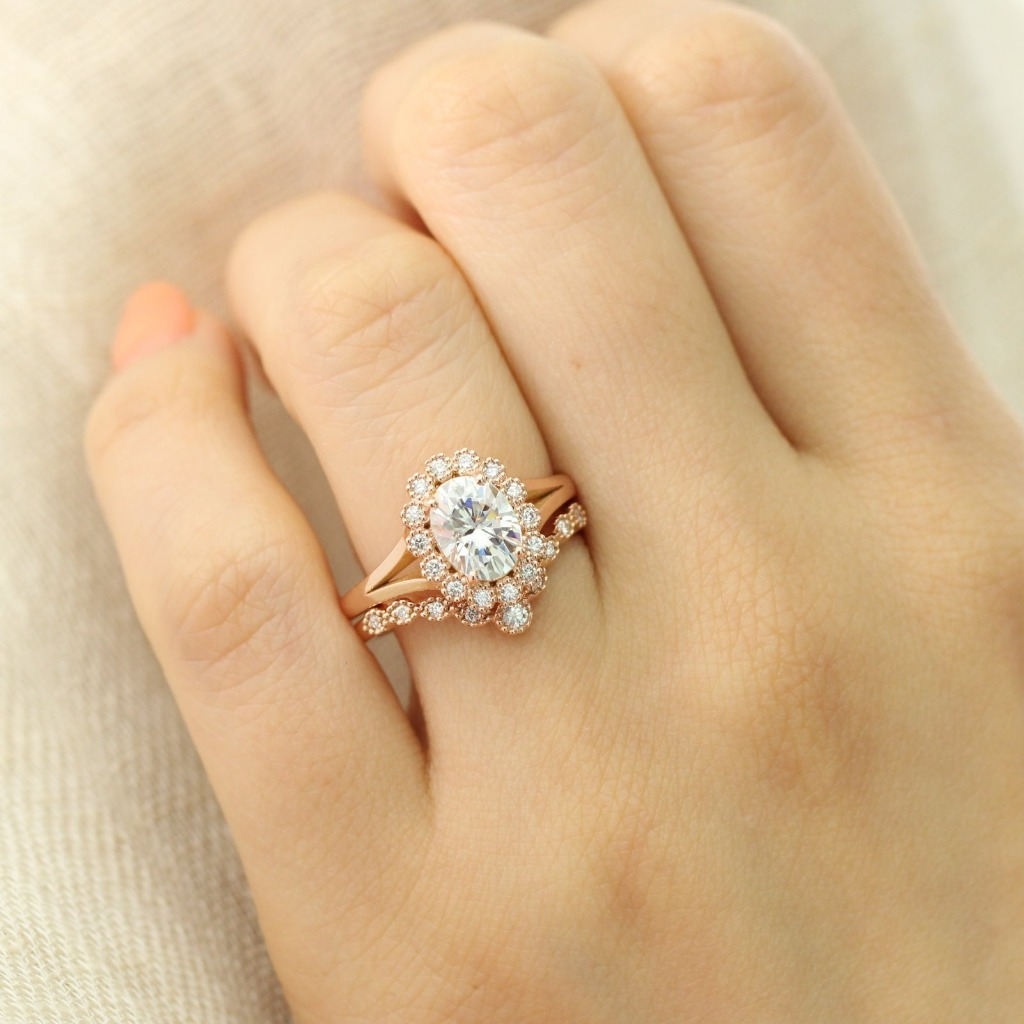 Artfully sculpted bridal ring set of a vintage inspired engagement ring with an oval cut moissanite in 14k rose gold halo diamond ring