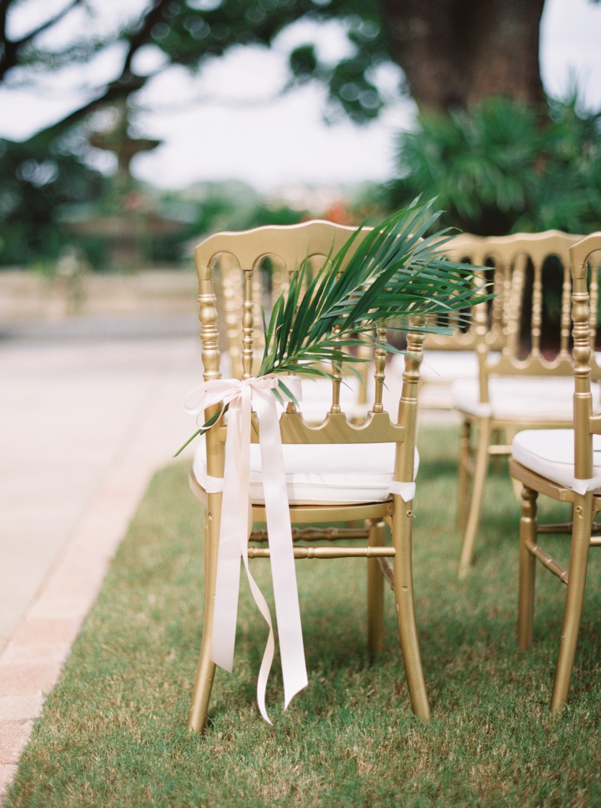 gold chair with palm leaf tied to it