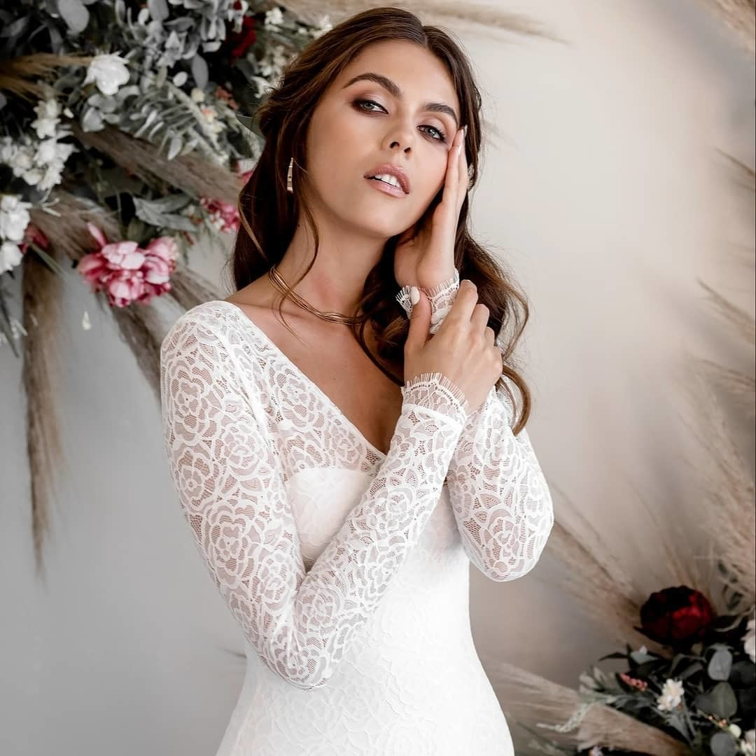 Long lace sleeves embellished with Chantilly eyelash trim, an illusion lace neckline with sweetheart lining, a deep open back, and