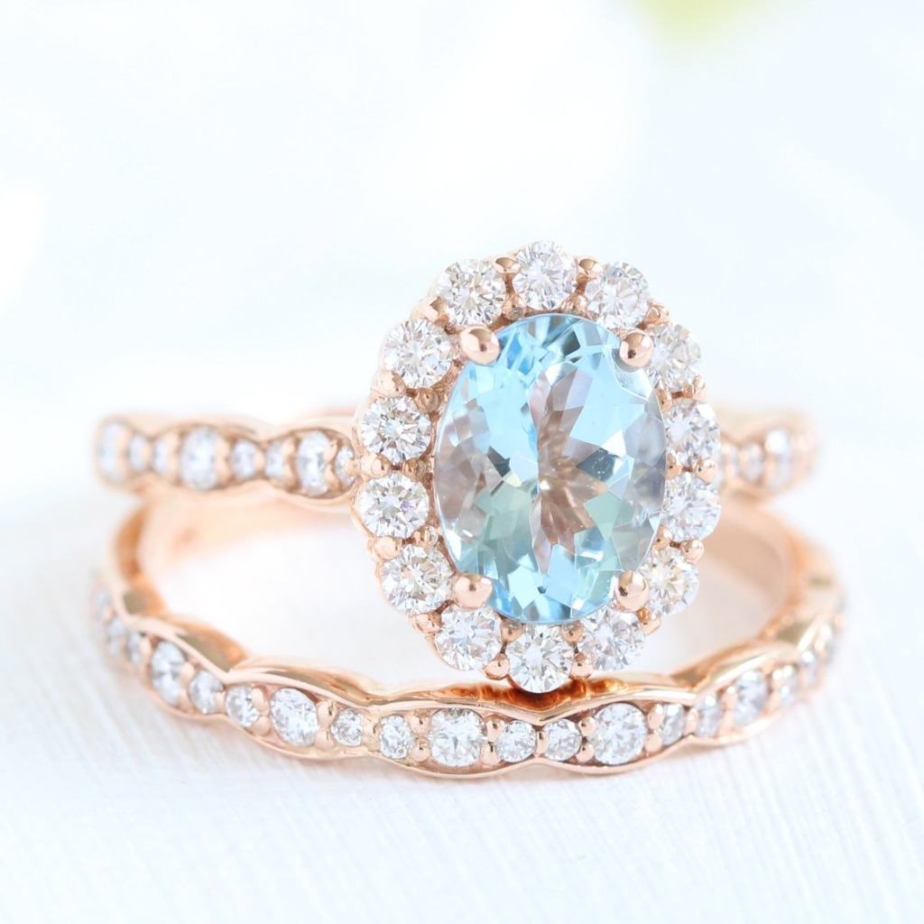 Vintage-style bridal set featuring an oval aquamarine engagement ring in 14k rose gold halo diamond ring setting pairs gorgeously with