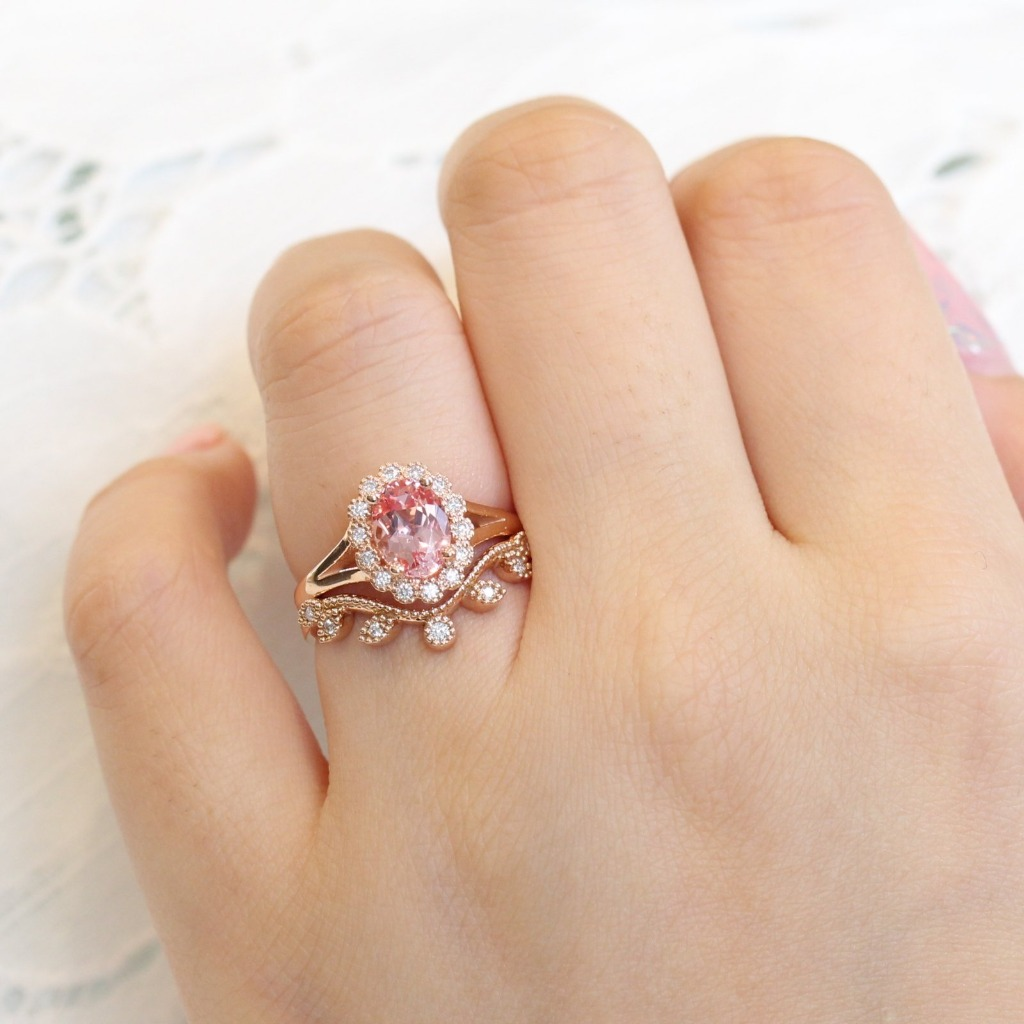 This unique vintage inspired sapphire bridal set showcases an oval cut peach sapphire engagement ring set in a 14k rose gold vintage