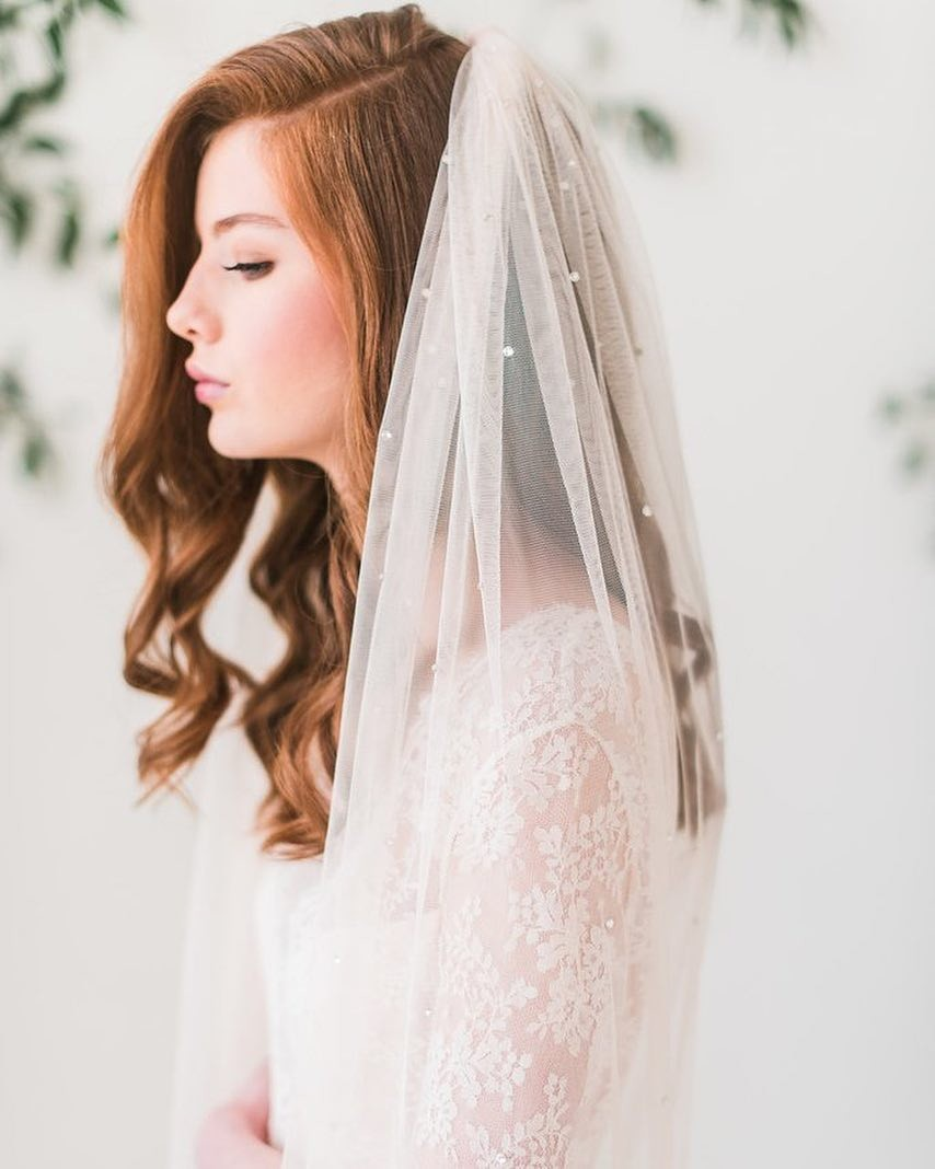 Our bridal veil with cascading crystals features soft English net, swarovski crystals and a wire comb. Photo by